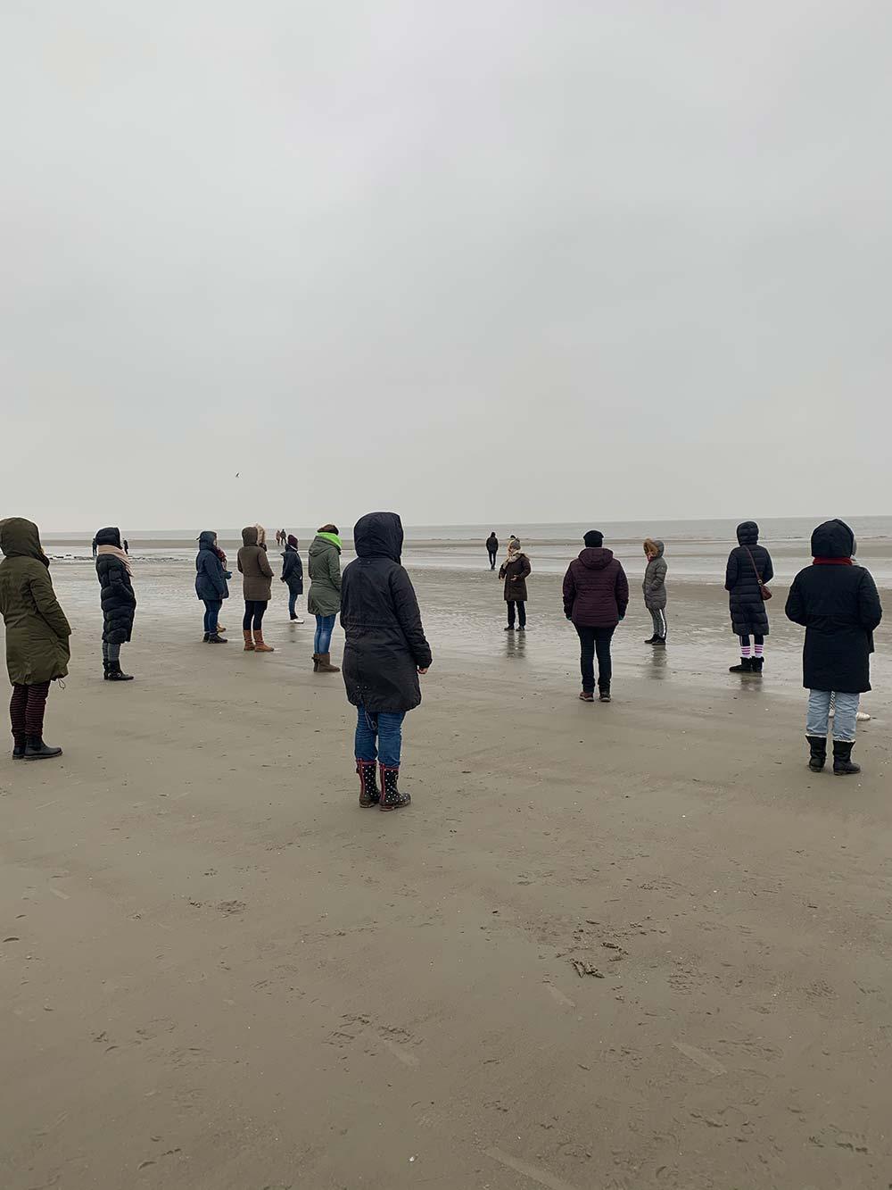 Alle Teilnehmer schauen am Strand auf die winterliche Nordsee